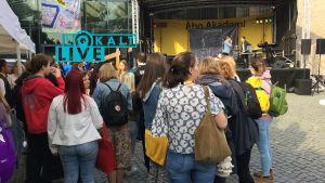 En samling människor följer med program på en scen.