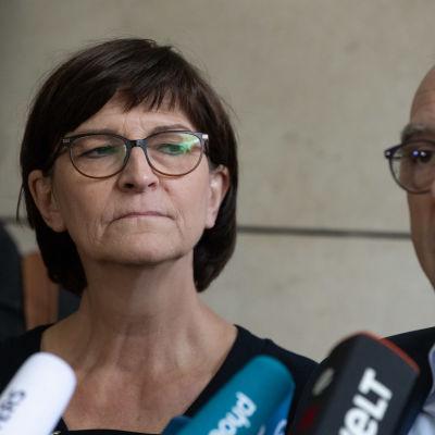 Saskia Esken och Norbert Walter-Borjans på en presskonferens. Bara deras ansikten syns, med några mikrofoner i nedre delen av bilden.