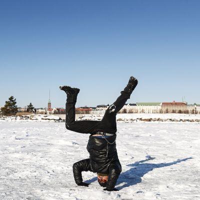 En man står på huvudet i solen på isen vid en strand