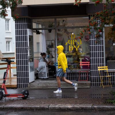 En man i gul regnrock promenerar i regn i Berghäll i Helsingfors.