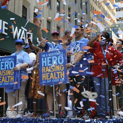 Ett gäng människor med skyltar som tackar för hälsovårdarnas arbete under coronapandemin. Runt människorna ses mängder med konfetti.