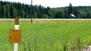 En stolpe med information om ett gasrör som är nedgrävt på platsen. Grön äng.