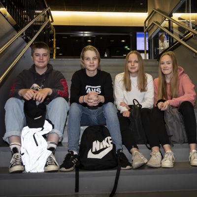 Neljä nuorta istuu portaikossa.