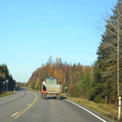 Traktor kör på väg.