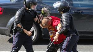 Två kravallpoliser griper en man som håller i en blombukett