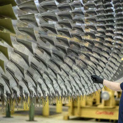 En arbetare poserar bredvid en gasturbin på Siemens fabrik i Berlin.