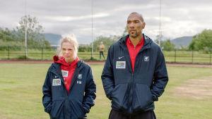 Helena och Michael står på träningsplanen med händerna i fickorna.