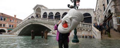 Person står på översvämmad gata och håller i en jättestor mask.