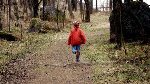 Barn springer i skogen.