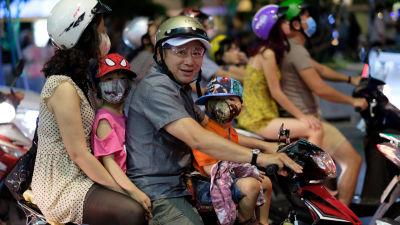Perhe matkustaa skootterilla Vietnamin suurimmassa kaupungissa Ho Chi Minh Cityssa.