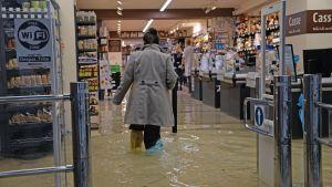 Kvinna går i översvämmad supermarket.