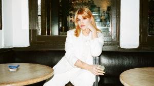 Författaren Tone Schunnesson sitter i en soffa på ett café, klädd i vitt.