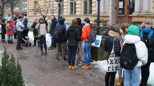 Ett tjugotal unga människor står utanför stadshuset i Borgå, ett gult stenhus.