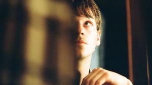 Louis kikar fram i en dörröppning så att halva ansiktet är i skugga.