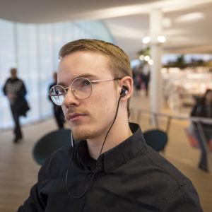 Mies kuuntelee äänikirja Hkin pääkirjastossa Ooodi