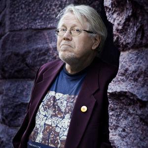 författaren Lars Sund står invid ett berg