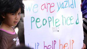 """""""Vi är yazidier vi behöver hjälp, hjälp, hjälp"""" står det på skylten som en liten flicka visar upp under påvens besök i Moria-lägret på Lesbos"""