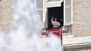 Påven Franciskus hälsdar från en balkong.