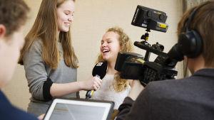 En intervjusituation med en kameraman på plats för att filma.