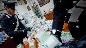 Italienska poliser kontrollerar beslagtagna falska eurosedlar.