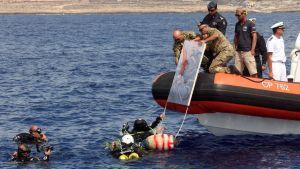 Dykare lägger ner ett minne för tragedin utanför Lampedusa i havet. Den 3 oktober var det ett år sedan katastrofen.