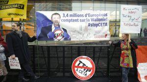 """Aktivister som motsätter sig frihandelsavtalet Ceta med Kanada, visar upp en banderoll med en bild av premiärminister Paul Magnette och texten """"3,4 miljoner europeer litar på Vallonien."""""""
