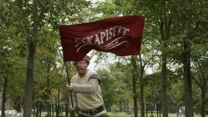 näyttelijä Niko Taskinen puistossa sarvikypärä päässä Eskapistit lippu kädessä
