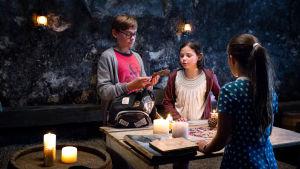 Barnen i serien Piratskattens hemlighet har samlats kring ett bord och diskuterar.