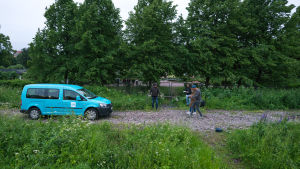 Vehreässä maisemassa Ylen turkoosi auto ja Toivon yön työryhmää.