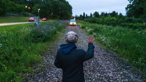 Juha Rosma viittelöi autolle soratiellä.