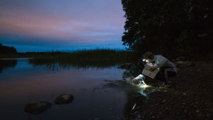 Paavo Kinnunen läiskyttää vettä öisellä rannalla.
