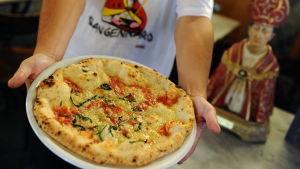 Mies ojentaa lautasta, jolla pizza, vieressään Napolin suojeluspyhimystä San Gennaroa esittävä pysti.
