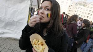 En belgisk kvinna äter pommes frites under en demonstration mot de misslyckade regeringsförhandlingarna år 2011.