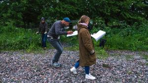 Petja Lähde ja Saija Lentonen kävelevät soralla, Pekka Savolainen puomittaa.