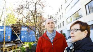 Pekka ja Arja Huhmarniemi talon pihalla, kontit takana.