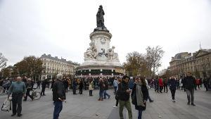 Folk lägger blommor vid Place de la Republique i Paris.