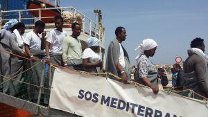 Flyktingar går i land i Lampedusa efter att ha räddats ur havet av fartyget Aquarius.