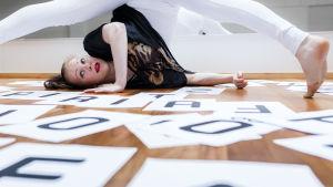 Pirita Tuisku tanssii paperikirjainten keskellä.