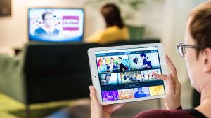 Taustalla nainen katsoo tv-ruutua, etualalla nainen selaa tv-tarjontaa tabletilta.