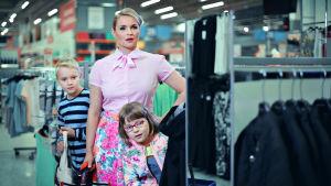 Vaaleanpunaiseen pukeutunut nainen, Neiti Etiketti, seisoo vaatekaupassa vaaterekkien välissä kahden lapsen, vaaleatukkaisen, raitapaitaisen pojan ja tummahiuksisen silmälasipäisen tytön kanssa.