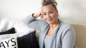 Johanna Pakonen istuu sohvalla ja hymyilee kameralle.