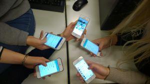 Ungdomar som surfar på sina smarttelefoner.