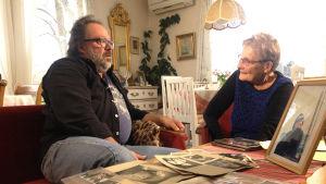 Dick med sin faster vid ett bord fyllt av fotografier.