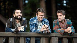 kolme miestä nojaa parvekkeeseen.