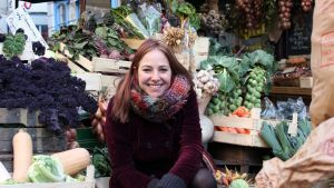 Nainen istuu hedelmäkojun keskellä.