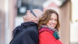 Nainen ja mies nojaavat toistensa selkiin. Nainen katsoo kameraan, mies ylöspäin.