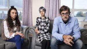 kaksi naista ja Theroux istuvat sohvalla ja katsovat kameraan.