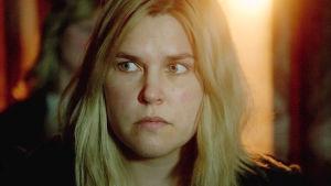 Karaktären Vera i närbild med skrämd blick och ett starkt ljus i bakgrunden.