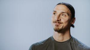 Zlatan katsoo vasempaan yläviistoon hymyillen.