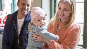 Nainen pitää vauvaa käsissään hymyillen. Takavasemmalla mies katsoo vauvaa myös hymyillen.